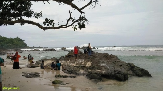 pasir-putih-halus-berlatar-batu-lava-volkanik-bergurat
